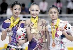 CHRYSTAL Lim (tengah) meraikan tiga pingat emas yang dimenangi dalam acara gimrama tali, belantan serta reben, sambil diapit oleh Foong Seow Ting (kanan) dan peserta Thailand, SrideeTharatip