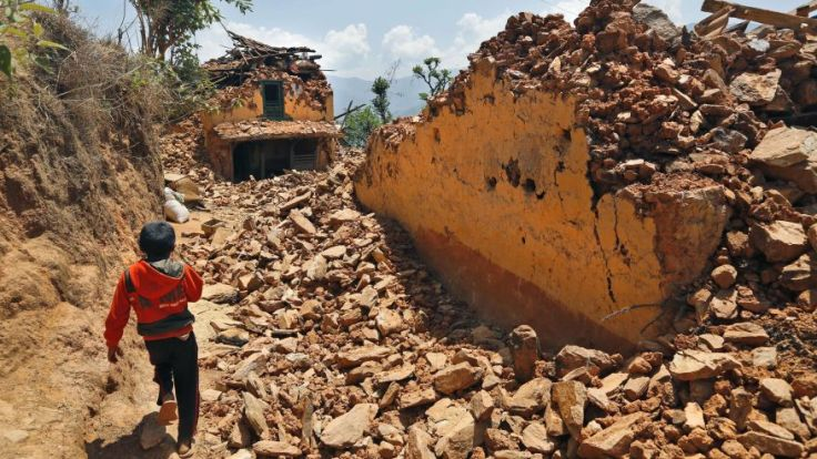 Source : Foxnews.com May 2, 2015: A Nepalese boy runs past houses destroyed by last week's earthquake in Pauwathok village, Sindhupalchok district, Nepal. (AP)